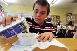 SCHOOL BREAKFAST: James Murray, 9, prepares to eat breakfast in class, Monday Sept. 30, 2013, at the Egg Harbor City Community School. The district is among most improved statewide in offering breakfast since they began including it in school day for all children. - Michael Ein