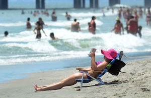 Heatwave: Antoinette Piliro of Philadelphia reads a book by the water's edge on the beach at MLK. Monday July 15 2013 People escape the heat on the Atlantic City beach near Kentucky and MLK Blvd.(The Press of Atlantic City / Ben Fogletto) - Photo by Ben Fogletto