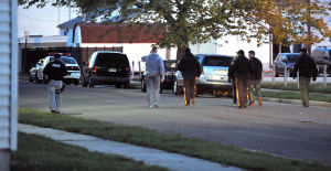 AC RAID: AC Police personnel walk down North Virginia Avenue Tuesday during a pre-dawn raid. The area is known for drug dealing.  - Michael Ein