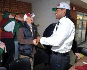 Mitchell Photo: Cedar Creek High School's Damon Mitchell, right, of Mays Landing, is congratulated by Pirates wide receivers coach Mike Forest, of Mays Landing, on Wednesday after the quarterback signed a letter of intent to attend the University ofArkansas. - Michael Ein