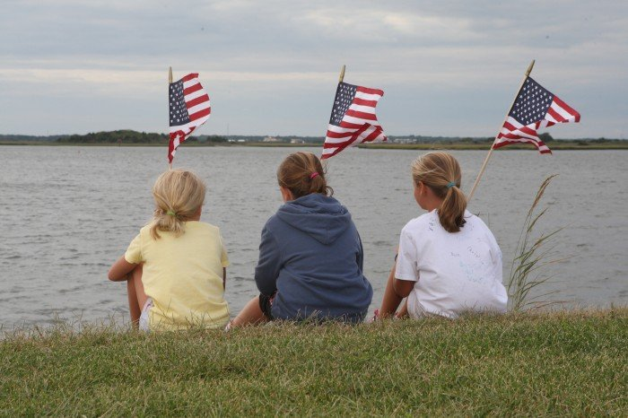Julia Sorensen, 7, of Wildwood Crest, Bella Ferraco,9 of Wildwood Crest, and Lauren Sorensen, 9, of Wildwood Crest, take a break from placing flags along Sunset Lake in Wildwood Crest in preparation for marking Sept. 11th.    This photo was taken by Michael Martin.