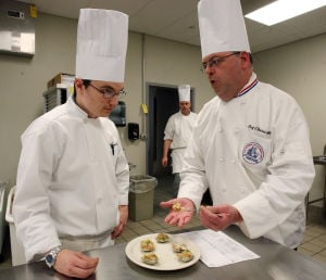 : Culinary instructor Jon Davies of West Cape May, (right) grades the dish created by Jon Thompson of Dennis Township. The Cape campus of Atlantic Cape Community College in Cape May Court House, now offers a Culinary Arts Training Program. Wednesday April 3, 2013. (Dale Gerhard/The Press of Atlantic City)  - Dale Gerhard
