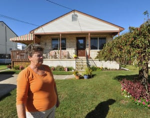 FLOOD INSURANCE: Margaret Lynn stands in front of her ranch-style house Friday in Brigantine. Her flood insurance premium was raised this year from $523 to $6100 - Photo by Michael Ein