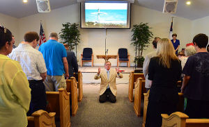 J10 Brigantine Bible Church: 'Pastor Bill' Davis (center) conducts the service in the finished sanctuary. Sunday June 9 2013 Rededication service and dinner to celebrate reopening of the Brigantine Bible Church, which was heavily damaged by Sandy. The congregation was rebuilding for 6.5 months, and meeting in the Brigantine Community Center for all that time. (The Press of Atlantic City / Ben Fogletto)  - Ben Fogletto