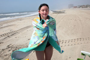 Cold Water: Michaela Sykes, of Philadelphia, Pa., warms up in a towel after leaving the chilly water off the beach near Gladstone Avenue, in Margate, NJ, Wednesday July 10, 2013. Water temperatures for the ocean have been colder than usual this summer, a bummer for beachgoers. - Vernon Ogrodnek
