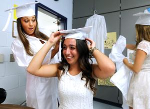 OCHS Graduation: Marisa Holt, 17, left of Marmora help Rachel Fichetola, 18 of Ocean City, right with her cap before the start of Ocean City Graduation Friday, June 20, 2014. - Edward Lea