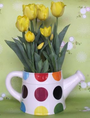 Create Fresh-cut Flower Bouquets For Mother's Day: Yellow tulips look playfully young in a bright polka-dot watering crock.