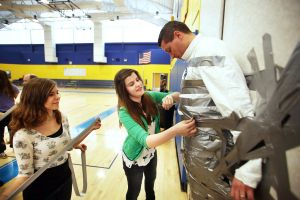 BOOK THE PRINCIPAL: Jocelyn Schwartz, 14, left and Alyx Stormes, 14, middle students at Northfield Middle School duct-taping principal Glenn Robbins to the gym wall and covering him in book covers as part of school challenge Friday, Feb 2, 2014. - Edward Lea