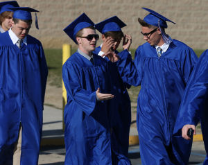 Hammonton High School Graduation: Dylan Reese, left, and Kieley Cook, both 18 of Atco, slap hands as they march to Hammonton High School's graduation, Friday June 20, 2014, in Hammonton. - Michael Ein