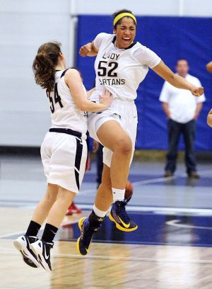 A: Holy Spirit's Gina Lewis (52) celebrates with teammate Brianne Long after Lewis hit the game-winning basket against Sacred Heart during Saturday's Cape-Atlantic League final.  - Staff photo by Edward Lea
