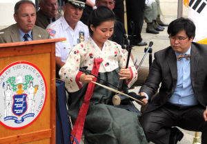 KOREAN WAR VETS: Heain Kim, of Somers Point, plays the haegeum, a traditional Korean string instrument, during the Commemorative Ceremony, hosted by the New Jersey Korean War Veterans Association, at the Korean War Memorial at Brighton Park, in Atlantic City, NJ, Friday July 26, 2013. - Vernon Ogrodnek