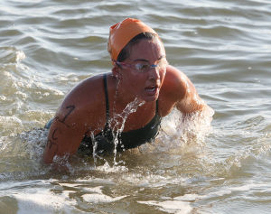 : Cape May's Kerry Choplin, exits the water at the end of the swim. Cape May Point Women's Lifeguard Challenge, a short run-paddleboard-swim triathlon for women lifeguards Monday July 29, 2013. (Dale Gerhard Photo/Press of Atlantic City) - Dale Gerhard