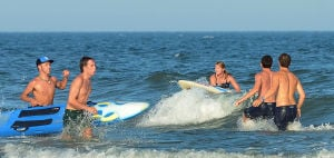Tri-Resorts: Upper's Taylor Hennessy (center) prepares to dismount her board during the Paddle Board Relays. Monday July 15 2013 Tri-Resorts Lifeguard Championships in Strathmere. (The Press of Atlantic City / Ben Fogletto) - Photo by Ben Fogletto
