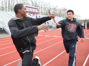 A: Pleasantville's Isaac Clark, 18, left, and Dagoberto Arias, 18, practice their baton exchange during a workout for their 4x800 relay at Pleasantville High School on Tuesday. Clark and Arias have known each other since they were young.  - Staff photo by Edward Lea