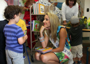 Miss NJ In Margate: Cara McCollum, Miss New Jersey, originally from Forrest City, Arkansas, talks with Henry Riegler, visiting from Philadelphia, PA, as she hands out books to children at the Margate Library, in Margate, Wednesday July 10, 2013. - Vernon Ogrodnek