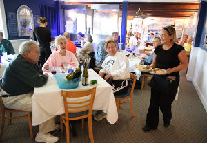 ATS Mothers Day Roundup: Guests Harold and Betty Rupert and daughter Marcella McCarthy, all of Ocean City eye the dished being carried by server Dayna Cramsey of Sea Isle (right). Friday May 2 2014 Mildred's Strathmere Restaurant, Strathmere. (The Press of Atlantic City / Ben Fogletto) - Ben Fogletto