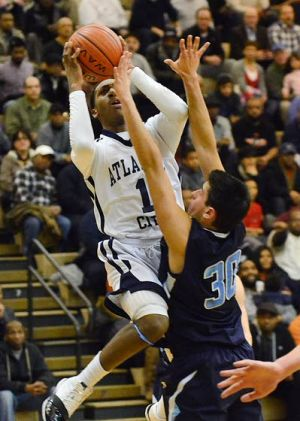 Top-ranked Atlantic City Grinds Way Past No. 3 Prep: Isiah Graves leaps to take a shot for the Vikings over St. Augustine Prep's Joe Gatto during their Battle by the Bay game Friday night in Atlantic City.