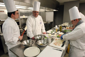 : Culinary instructor Jon Davies of West Cape May, (center) watches over the preparation of dishes by Jon Thompson of Dennis Twp. (left) and Brian Bender of Rio Grande (right). The Cape campus of Atlantic Cape Community College in Cape May Court House, now offers a Culinary Arts Training Program. Wednesday April 3, 2013. (Dale Gerhard/The Press of Atlantic City)  - Dale Gerhard