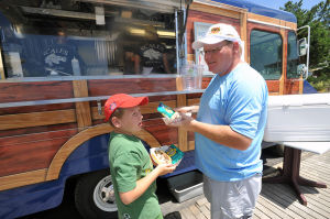 SCALES BACK: John Norris and son Colin, 9, of Windsor Locks, CT., order food from the Scales Restaurant food truck. - Michael Ein