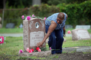 Sister Jean Ceremony: Pastor Cecelia Woodard, Jean Webster's daughter originally from Atlantic City and now residing in Jackson, MS, places a flower on her mother's grave during a dedication of Sister Jean's headstone at the Atlantic City Cemetery, in Pleasantville, NJ, Thursday, Aug, 22, 2013. - Vernon Ogrodnek