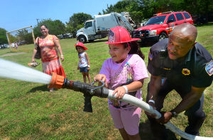 Cookout: Priscilla Rivera, 7, sprays a firehose with Capt. Lionel Fonville of EHT, Fire Marshall with the ACFD as her cousin Emily Mercado, 5, and mother Jackie Rivera watch. The family are all from Atlantic City. Tuesday July 16 2013 Atlantic City sponsored cookout at Chelsea Field at Filbert and N. Annapolis. (The Press of Atlantic City / Ben Fogletto) - Ben Fogletto