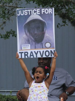 Zimmerman: Hanna Brianna, 5, holds a sign in front of her home in the Goldsboro Historical neighborhood, Saturday, July 13, 2013, in Sanford, Fla. while residents waited for word on the verdict in the George Zimmerman trial. Zimmerman is charged with the 2012 shooting death of Trayvon Martin. He was acquitted late Saturday night.