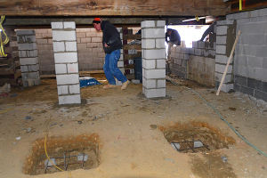 How To Raise A House: New supports for the home (rear) and holes ready for cement where more supports will constructed under the house. Friday February 1 2013 Steve Huack's construction business specializes in moving homes. Now because of FEMA flood recommendations, he is raising homes to meet the new standards. Work on home on Bayshore Avenue in Brigantine. (The Press of Atlantic City / Ben Fogletto)  - Photo by Ben Fogletto