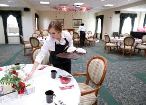 REAL ESTATE: Sarah Cheafsky, of Ocean City, prepares tables, Friday Feb. 14, 2014, for a special Valentines event at The Shores at Wesley Manor, in Ocean City. The community, completely rebuilt and renovated in 2006, features two dining rooms, a bistro, library, customized fitness programs, exercise room, gift shop, and chapel. (Staff Photo by Michael Ein/The Press of Atlantic City) - Michael Ein