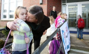 Stone Harbror: Stone Harbor Mayor Suzanne Walters gives a kiss to second-grade student Isadora Bosacco on Monday before entering the Stone Harbor Elementary School. The building reopened for the first time Monday morning since being flooded and closed from Hurricane Sandy.  - Dale Gerhard