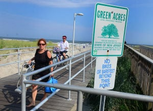 Open Space: Randi Weinerman of Ventnor (left) passes a sign designating the pier as a Green Acres site. Monday July 29 2013 Ventnor Pier related to open space measure that was up for a vote in the senate on Monday. (The Press of Atlantic City / Ben Fogletto) - Ben Fogletto