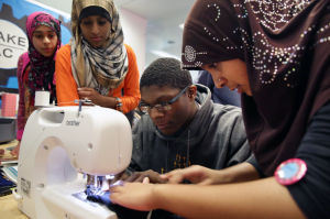 MAKER SPACE: Asthma Hai, 15, right, shows Umoja Blanks, 16, how to use a new sewing machine as Isha Malik, 14, right, and Ramsha Malik, 19, watch, Monday April 14, 2014, at The Atlantic City Free Public Library's new Teen Maker Space in Atlantic City. (Staff Photo by Michael Ein/The Press of Atlantic City) - Michael Ein