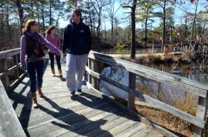 Birch Grove Park: Alexandria Manno, 19, of Somers Point; Morgan Owens, 19, of Somers Point; and Dennis Gibson, 21, of Egg Harbor City, stroll across one of the scenic bridges on the nature trails Tuesday at Birch Grove Park in Northfield.  - Staff photo by Danny Drake