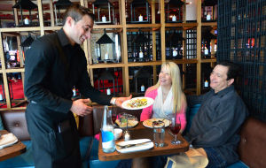 Restaurant Week: Amada server Antonio Gracia, of Egg Harbor Township, delivers an entree to Renee Moro and Neil Nasta, of Hersey Pa., Saturday. The restaurant in Revel is one of 79 scheduled to take part in Atlantic City's Restaurant Week this year.  - Ben Fogletto