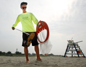 No Beach Raking: Cape May Point beach tag checker Austin Schwartz of Cape May Point, picks up trash on the beach using grabbers and a bag. Cape May Point gave up machine raking the beach, a practice that results in a sterile strand with no seashells, shorebirds, plants and other natural beach ecosystem features. Instead of tractors towing rakes, beach tag checkers pick up debris by hand each day. Wednesday Aug. 28, 2013. (Dale Gerhard Photo/Press of Atlantic City) - Dale Gerhard
