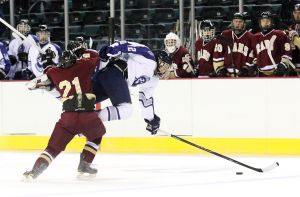 St. Augustine Beats Gloucester Catholic: St. Augustine's Michael Gaimari, right, leaps over Gloucester Catholic's Andrew Dolan, left, for the puck during hockey game at Boardwalk Hall in Atlantic City on Tuesday. - Edward Lea