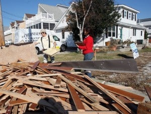 Restoration 1: Lisa Quirk, right, and her son Kyle, of Colonial Carpet Cleaning and Restoration, pile stripped-out debris from a home in Sea Isle City their company is restoring after Hurricane Sandy.  - Photo by Dale Gerhard