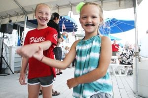 NIGHT IN VENICE: Carly Hollenbach, 9 , left and friend Ellie McIntyer, 5 right take part in mustache theme party during Night in Venice boat parade in Ocean City Saturday, July 20, 2013. - Photo by Edward Lea