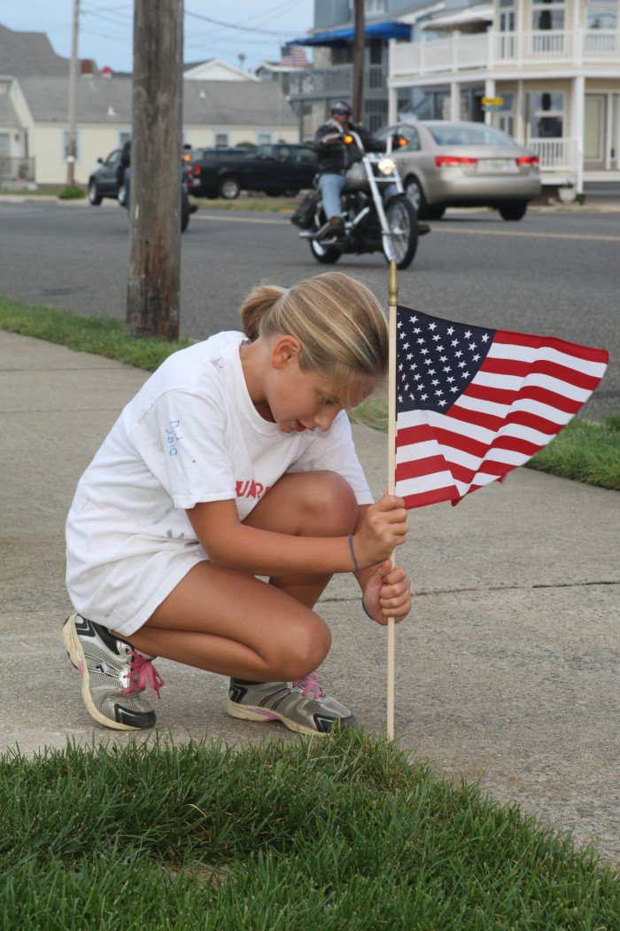 Lauren Sorensen, 9, of Wildwood Crest places flags along Sunset Lake in Wildwood Crest in preparation for marking Sept. 11th.  This photo was taken by MIchael Martin.