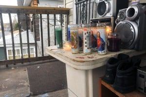 COUNTY VIOLENCE: Candles burn Friday in memory of Taron Williams, 19, and Todd Mitchell, 13, at the Woodland Avenue, Pleasantville, home where they were fatally shot Wednesday.   - Photo by Michael Ein