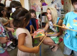 Miss NJ In Margate: Cara McCollum, Miss New Jersey, originally from Forrest City, Arkansas, hands out books to children at the Margate Library, in Margate, Wednesday July 10, 2013. - Vernon Ogrodnek