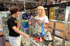 Hollywood Smokin: From left, Stacey Miller, of Margate, sales associate, and Kim Betsh, of Margate, owner of Hollywood Smokin', in Northfield, a huge retail store that caters to smoking products in an age of anti-smoking fervor, Friday May 31, 2013. Betsh is holding a custom-made glass recycler made by Hamm Brushland that is valued at over $10,000The store also has time for under $10.  - Photo by Vernon Ogrodnek