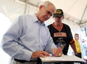 Vetrock: Vietnam War vets. Lt. Col Oliver North, left the keynote speaker gives Robert Manuel , right of Woodberry NJ autograph during VetRock 2013 outdoor festival at Bader Field in Atlantic City Saturday, June 1, 2013.  - Photo by Edward Lea