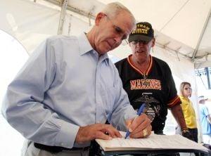 Vetrock: Vietnam War vets. Lt. Col Oliver North, left the keynote speaker gives Robert Manuel , right of Woodberry NJ autograph during VetRock 2013 outdoor festival at Bader Field in Atlantic City Saturday, June 1, 2013.  - Edward Lea