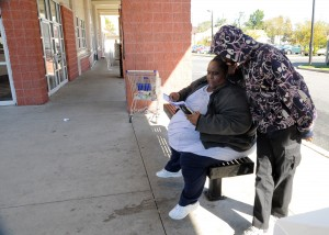 Transportation: Coretta Hinton, 40, and her son, Kito Hinton, 18, both from Vineland, check the bus schedule while waiting for their bus Thursday at the NJ Transit Bus Terminal on Landis Avenue in Vineland.  - Dave Griffin