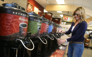 WaWa: Lori Yeager of Ocean City pours her coffee from the thermoses. Sunday April 13 2014 Customers buy coffee at the new WaWa on Rt 52 in Somers Point. WaWa will celebrate it's 50 year anniversary this week. (The Press of Atlantic City / Ben Fogletto) - Ben Fogletto
