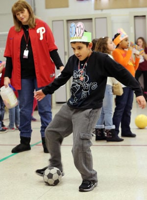 IN THE SCHOOLS CARNIVAL 100: Third grade student Joseph Leon, kicks a soccer ball during the activities. The Glenwood Avenue Elementary School in Wildwood, celebrated the 100th Day of School with sports-themed activities held in the school's all-purpose room. Tuesday Feb. 11, 2014. (Dale Gerhard/Press of Atlantic City) - Dale Gerhard