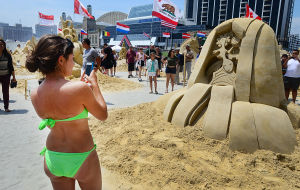 SAND SCULPTING: Mariel Isgard, visiting from Freehold Township NJ takes a picture of one of the entries. Sunday June 16 2013 World Championship of Sand Sculpting on the beach next to the Pier at Caesars in Atlantic City. (The Press of Atlantic City / Ben Fogletto)  - Photo by Ben Fogletto