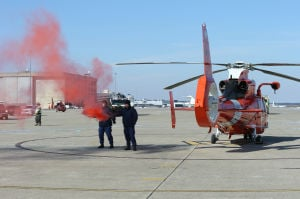 AIRPORT DISASTER DRILL: Gunner's mates Tyler Mace and Andrew Fortenbacher set off pyrotechnics to start the joint agencies mishap drill at the William J. Hughes Technical Center in Egg Harbor Township. - Photo by Michael Ein