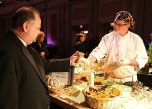 Presidents Charity Scholarship Ball: George Fisher, left, executive chef for the Atlantic City Convention Center and Boardwalk Hall, samples hors d'oeuvres from Sam Burgess, 17, of Smithville, Galloway Township, during the ball at Golden Nugget Atlantic City. - Ben Fogletto