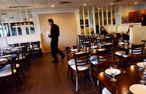 Tale Of Two Restaurants: Server Nick DeVito, of Margate, walks past the blocked-off entryway to the new under-construction area inside the original Johnny's Cafe in Margate, which is expanding in both directions while neighboring restaurant Fedeli's, a staple in town for decades, is permanently closed.  - Photo by Ben Fogletto